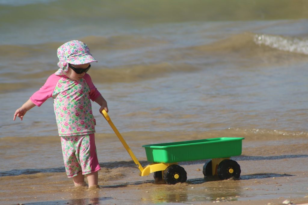 kid with trolly on toddler friendly beach Kauai